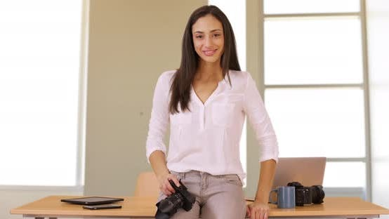 Thumbnail for A Latina photographer stands in her office with her camera