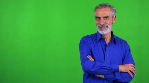 Cover Image for Old Senior Man Smiles To Camera with Folded Arms - Green Screen - Studio