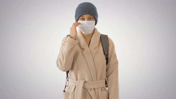 Girl in a Medical Face Mask Standing in a Coat on Gradient Background