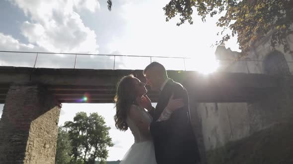 Thumbnail for Groom with Bride Near Old Castle Bridge. Wedding Couple. Happy Newlyweds