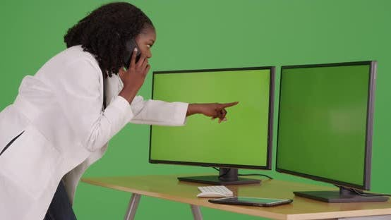 Thumbnail for Cute black female doctor talking on phone, looking at computer with green screen