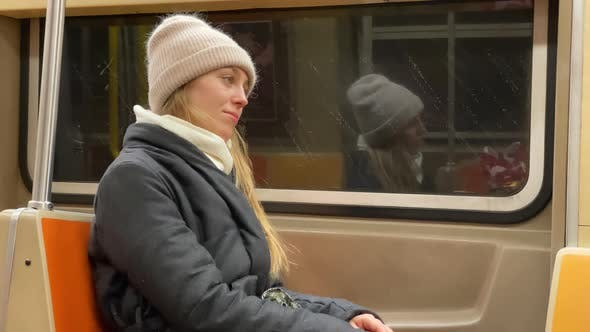 A Tired Young Woman on the Train in a Subway, Deep in Her Thoughts