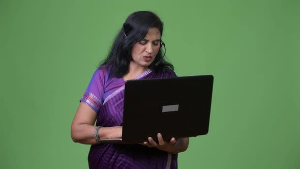 Thumbnail for Mature Beautiful Indian Woman As Call Center Representative Talking While Using Laptop