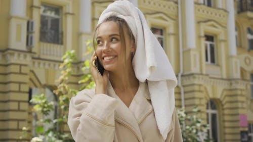 Porträt von Niedlich Lächeln Jou junge Frau im Bademantel mit Handtuch auf Kopf sprechen durch Handy
