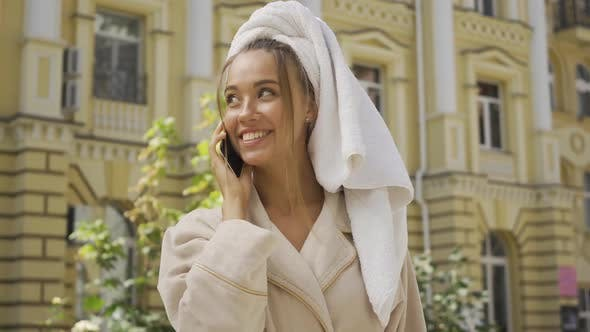Portrait of Cute Smiling Jou Young Woman in Bathrobe with Towel on Head Talking By Cellphone