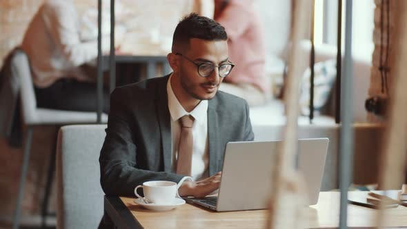 Thumbnail for Handsome Middle Eastern Businessman Working on Laptop in Cafe