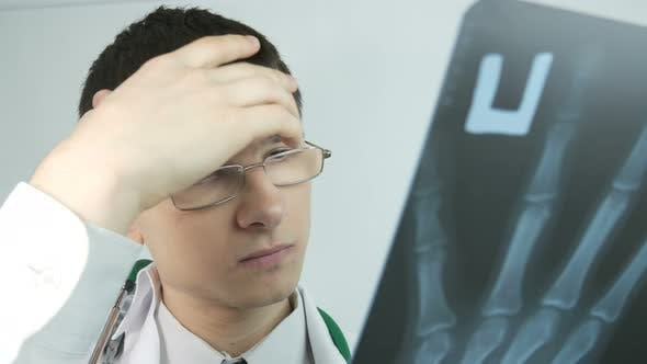 Thumbnail for Doctor Looks At X Ray Hands In The Office