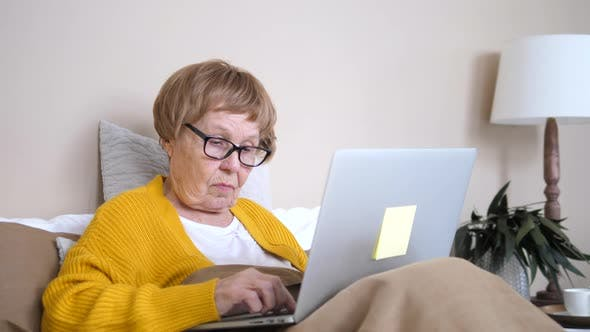 Seniors and Technology Concept. Elderly Woman Using Laptop Computer In Bed
