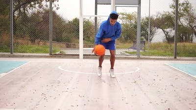 Young African American Practicing Basketball Outside