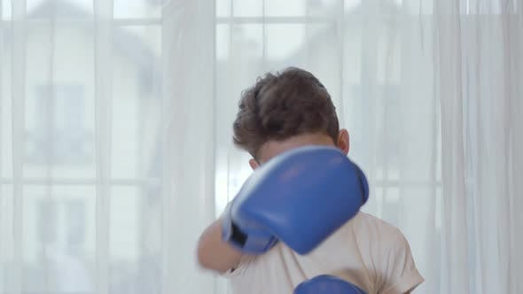 Thumbnail for Portrait of Young Caucasian Boy Boxing at Camera. Cute Schoolboy in Boxing Gloves Showing His Skills