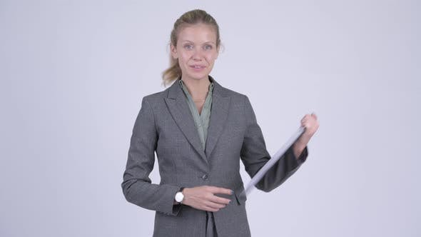 Thumbnail for Young Happy Blonde Businesswoman Showing Clipboard and Giving Thumbs Up