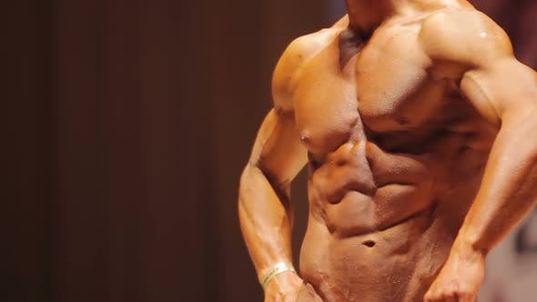 Man Demonstrating Ripped Bicep Muscles, Strong Torso at Bodybuilding Contest