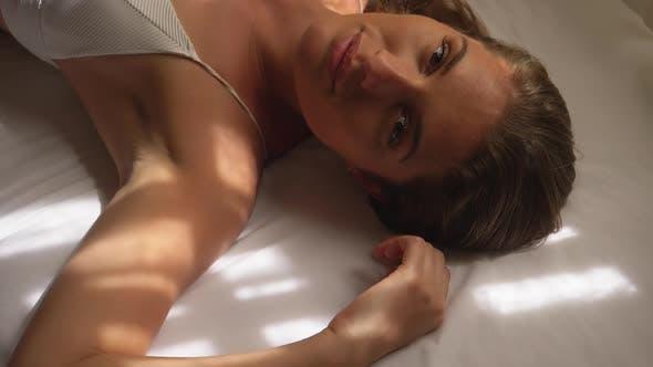 Wunderschöne weibliche Modell liegend auf weißem Bett mit einem Schäferlächeln