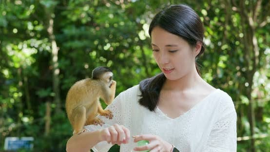 Thumbnail for Woman feed Squirrel Monkeys in the park