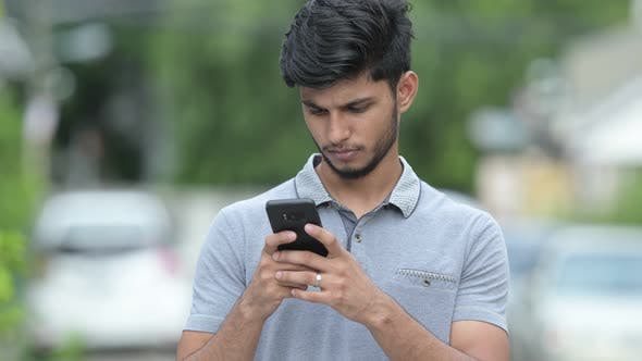 Thumbnail for Young Happy Bearded Indian Man Using Phone Outdoors