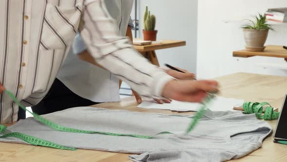Thumbnail for Fashion Designers Measuring T-shirt, Working at Their Workspace