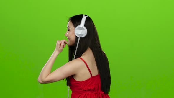 Thumbnail for Girl Listens To Cheerful Music Through Headphones and Dances. Green Screen. Slow Motion