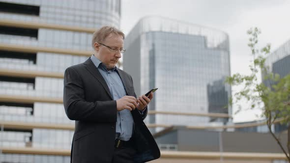Thumbnail for Man in Format Suit Texting on Smartphone, Adult Blond Manager or Businessman Outdoors by Office