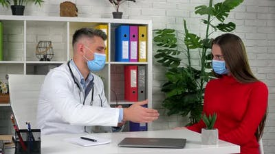 Doctor and patient in protective masks treats hand with antiseptic shake hands