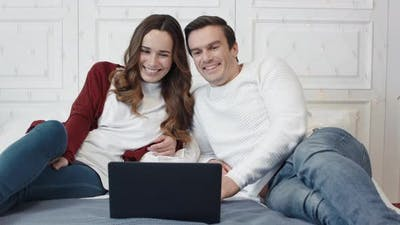 Happy Family Laughing in Front of Laptop Screen in Living Room