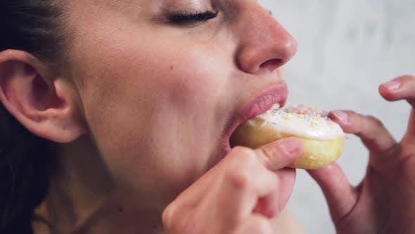 Woman Eating a Donut Closeup