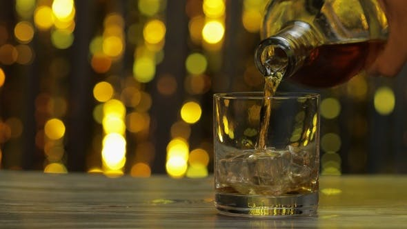 Pouring of Golden Whiskey, Cognac or Brandy From Bottle Into Glass with Ice Cubes. Shiny Background