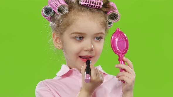 Thumbnail for Child in Curlers Holds a Mirror in Her Hands and Paints Lipstick with Lipstick. Green Screen