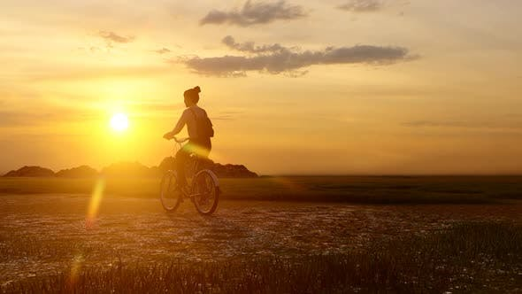 Thumbnail for Girl Wandering with Bicycle at Sunset