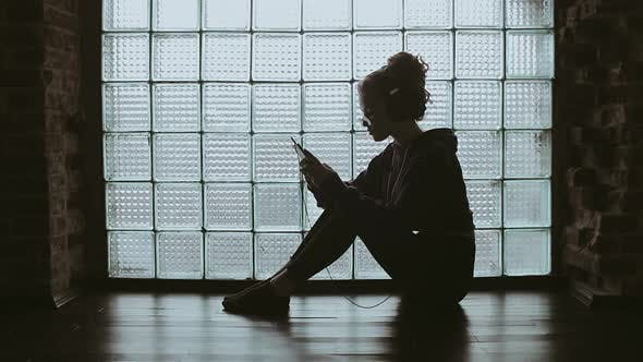 Thumbnail for Girl Sitting on the Floor Watching Video on Phone