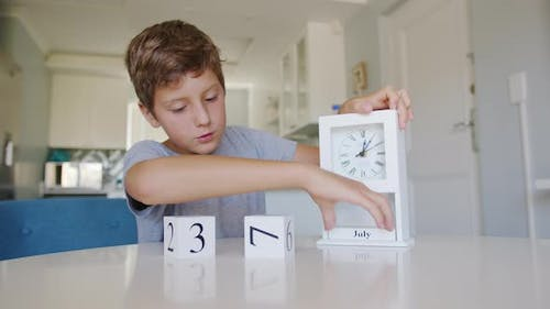 Boy Changing the Date on the Wooden Calendar on July 4 USA Independence Day