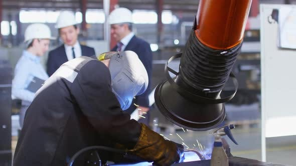 Thumbnail for Group of Engineers Looking at Worker Working with Welding Tool
