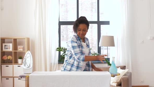 Thumbnail for African American Woman Ironing Bed Linen at Home 9