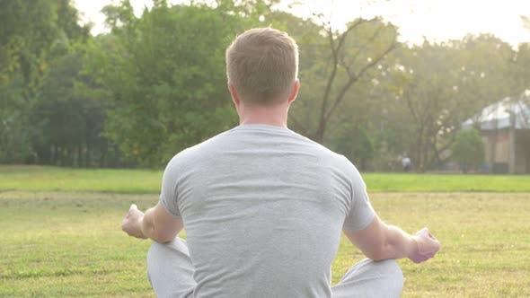 Thumbnail for Rear View of Young Man Meditating at the Park
