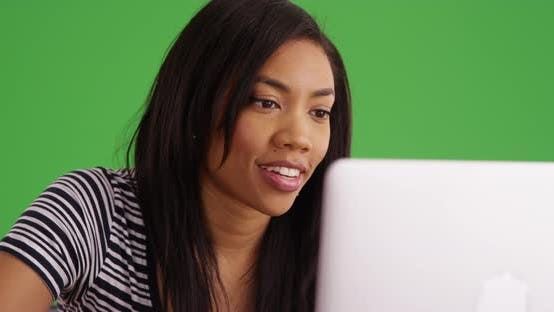 Thumbnail for Close up of black woman working on laptop computer on greenscreen
