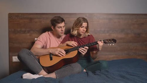 the Pair Play Acoustic and Electric Guitar Together. Beautiful Young Man Teaches His Girlfriend To