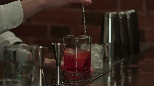 Professional Bartender at Work in Bar Mixing Ice and Liquor in Glass for Drink