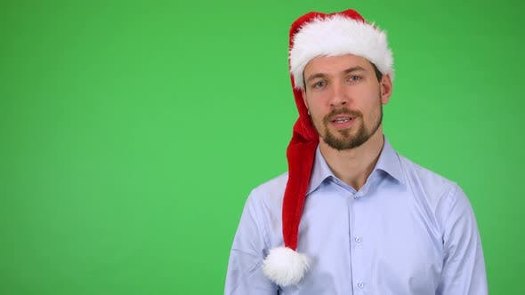 Cover Image for A Young Handsome Man in a Christmas Hat Talks Seriously To the Camera - Green Screen Studio
