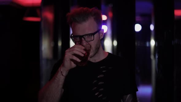 Thumbnail for Portrait of Relaxed Man Standing with Glass of Alcohol at the Disco Close Up. Man in Glasses Looking