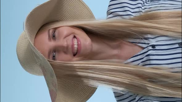 Beautiful Smiling Girl Putting a Hat on Her Head on Blue Background