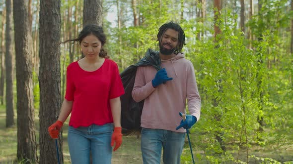 Multiracial Volunteer Couple Picking Up Litter in Forest