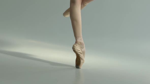 Slender Balarina Legs in Pointe Shoes Perform Pirouette Movements. Fascinating Dance