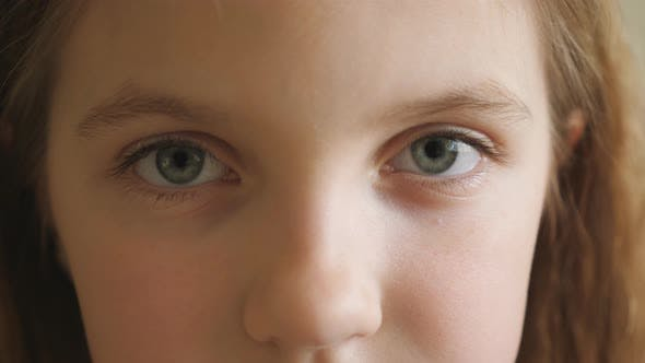 Thumbnail for Close Up Blue Eyes of Unhappy Small Blonde Girl Blinking and Looking Into Camera with a Tired Sight