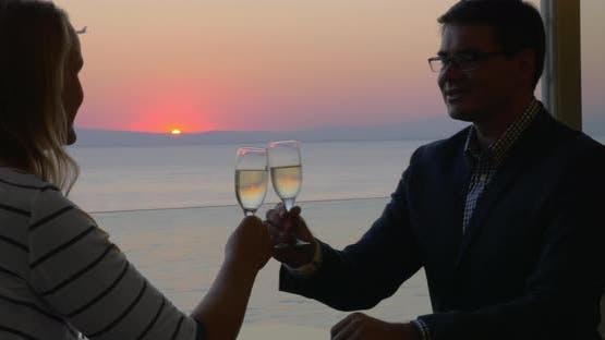 Loving couple enjoying romantic evening in seaside cafe