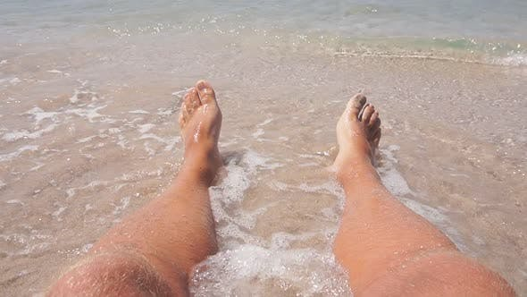 Closeup of a Man's Legs Lying on a Sandy Beach in Azure Sea Water Small Waves Beating Against His