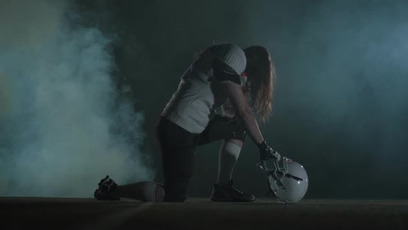 Cover Image for Portrait American Football Sportsman Player with Long Hair in Helmet Standing on One Knee