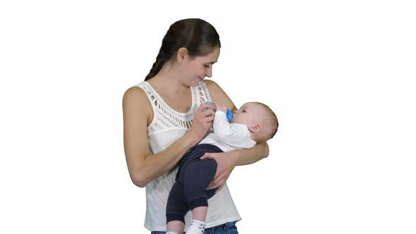 Thumbnail for Mother Gives Baby To Drink From Bottle on White Background.