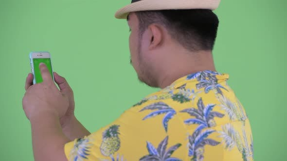 Thumbnail for Rear View of Happy Young Overweight Asian Tourist Man Using Phone