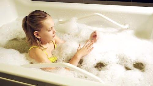 Petite fille prend la procédure dans un bain minéral