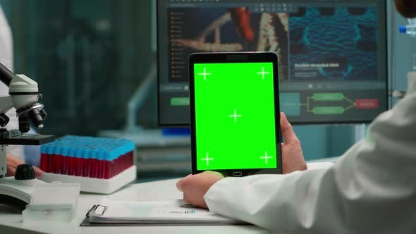 Thumbnail for Close Up of Biochemist Sitting in Laboratory Using Green Screen Tablet