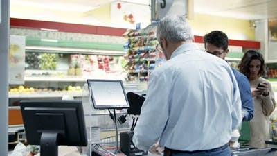 Cashier and Buyers at Cash Register in Supermarket